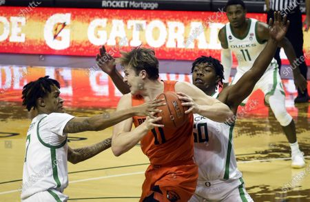 Oregon guard Jalen Terry (3) and Oregon forward Eric Williams Jr. (50) pressure Oregon State guard Zach Reichle (11) during the second half of an NCAA college basketball game in Eugene, Ore