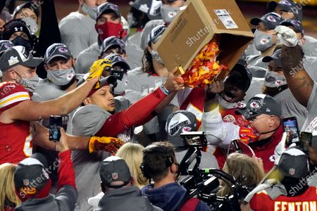 Kansas City Chiefs players dump a box of confetti on head coach Andy Reid after the AFC championship NFL football game against the Buffalo Bills, in Kansas City, Mo. The Chiefs won 38-24