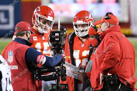 Kansas City Chiefs quarterback Patrick Mahomes (15) meets with Kansas City Chiefs head coach Andy Reid (right) and offensive coordinator Eric Bieniemy (second from right) during a break in play in the first half of the NFL AFC championship football game against the Buffalo Bills, in Kansas City, Mo