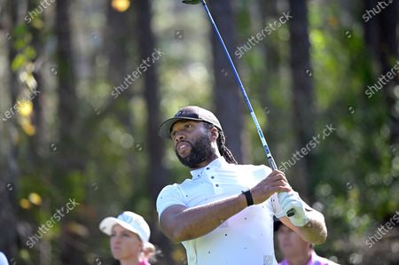 Football player Larry Fitzgerald watches his tee shot on the second hole during the final round of the Tournament of Champions LPGA golf tournament, in Lake Buena Vista, Fla