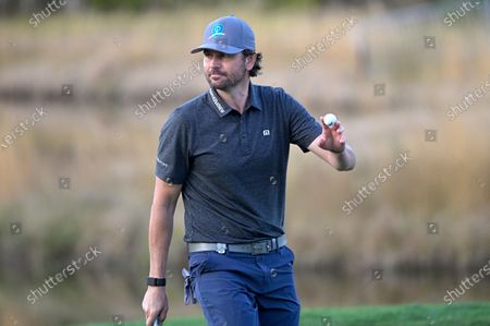 Former professional tennis player Mardy Fish acknowledges the crowd after making a putt on the 18th green to win the celebrity division of the Tournament of Champions LPGA golf tournament, in Lake Buena Vista, Fla