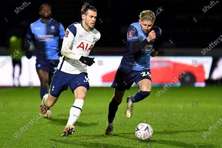 Stock Photo of Tottenham Hotspur forward (on loan from Real Madrid) Gareth Bale (9) sprints forward with the ball  under pressure from Wycombe Wanderers defender Jason McCarthy (26) during the FA Cup match between Wycombe Wanderers and Tottenham Hotspur at Adams Park, High Wycombe
