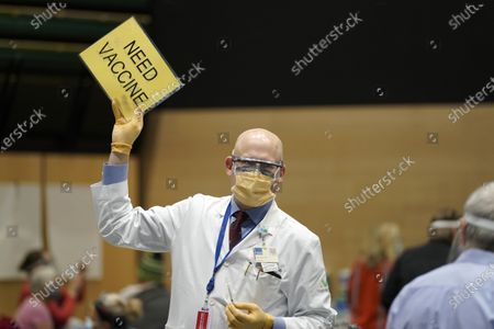 """Dr. John Corman, the chief clinical officer for Virginia Mason Franciscan Health, holds a sign that reads """"Need Vaccine"""" to signal workers to bring him more doses of the Pfizer vaccine for COVID-19, as he works at a one-day vaccination clinic set up in an Amazon.com facility in Seattle"""