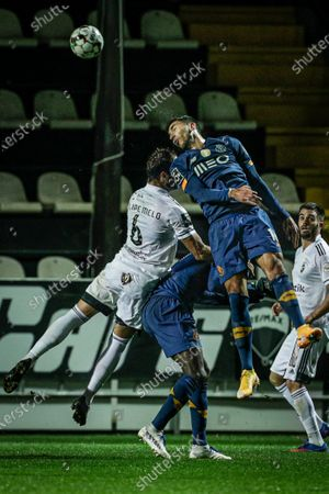 Farense player Filipe Melo (L) fights for the ball with FC Porto player Marko Grujic during the Portuguese First League soccer match between SC Farense and FC Porto held at Farense Stadium, Faro, Portugal, 25 January 2021.