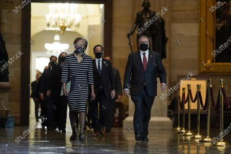 Clerk of the House Cheryl Johnson along with House Sergeant-at-Arms Tim Blodgett lead the Democratic House impeachment managers as they walk through Statuary Hall on Capitol Hill to deliver to the Senate the article of impeachment alleging incitement of insurrection against former President Donald Trump, in Washington, Monday, Jan. 25, 2021. Pool Photo by J. Scott Applewhite/UPI