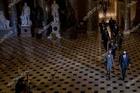 WASHINGTON, DC - JANUARY 25: US House Clerk Cheryl Johnson, US Representative Jamie Raskin (Democrat of Maryland)and US Representative David Cicilline (Democrat of Rhode Island) walk walk through the Capitol's Statuary Hall to deliver the article of impeachment for incitement of insurrection against former President Donald Trump to the Senate floor in Washington, DC. The House impeached Donald Trump for a second time with the Senate scheduled to begin its trial of the former president on February 8.