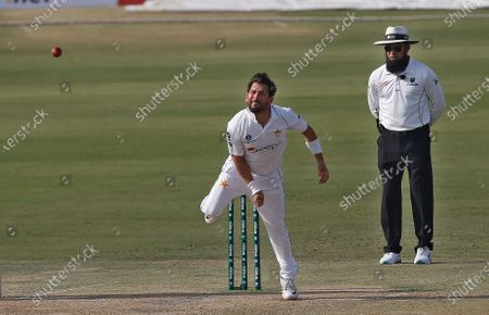 Pakistan's spinner Yasir Shah, center, bowls while umpire Aleem Dar watches during the first day of the first cricket test match between Pakistan and South Africa at the National Stadium, in Karachi, Pakistan