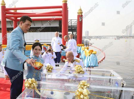 Thai King Maha Vajiralongkorn Bodindradebayavarangkun (L) accompanied by the Royal Consort Sineenat Wongvajirapakdi (2-L) release fishes into the Chao Phraya River during a merit-making ceremony to mark the Royal Consort's birthday at Wasukri pier in Bangkok, Thailand, 26 January 2021. Thai Royal Consort Sineenat was born on 26 January 1985.