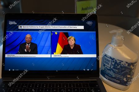 A screen shows German Klaus Schwab, left, Founder and Executive Chairman of the World Economic Forum, WEF, talking with German Chancellor Angela Merkel during a videoconference at the Davos Agenda, in Cologny near Geneva, Switzerland, 26 January 2021. The Davos Agenda, from 25 to 29 January 2021, is talking place in an online format due to the coronavirus pandemic.