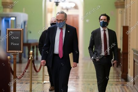 Senate Majority Leader Chuck Schumer, D-N.Y., walks to a news conference at the Capitol in Washington, . The senators will be sworn in later as jurors in the impeachment of former President Donald Trump