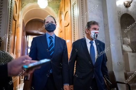 Stock Picture of Sen. Ron Wyden, D-Ore., left, and Sen. Joe Manchin, D-W.Va., leave the chamber after taking an oath and voting on how to proceed on the impeachment against former President Donald Trump, at the Capitol in Washington