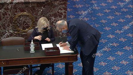 In this image from video, Sen. Chuck Schumer, D-N.Y., signs the oath book after being sworn in for the impeachment trial of former President Donald Trump in the Senate at the U.S. Capitol in Washington