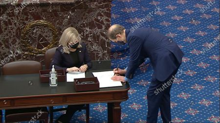 In this image from video, Sen. Ron Wyden, D-Ore., signs the oath book after being sworn in for the impeachment trial of former President Donald Trump in the Senate at the U.S. Capitol in Washington