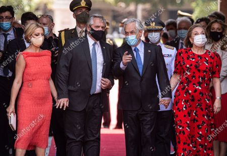 Argentina's President Alberto Fernandez, second from left, and his wife Marcela Luchetti are received by Chile's President Sebastian Pinera and his wife Cecilia Morel, upon their arrival to La Moneda presidential palace in Santiago, Chile, . Fernandez is on an official visits to Chile for two days