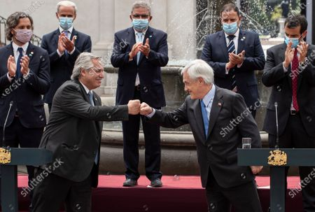 Argentina's President Alberto Fernandez, left, fist bumps Chile's President Sebastian Pinera as they make a joint statement at La Moneda presidential palace in Santiago, Chile, . Fernandez is on an official visit to Chile for two days