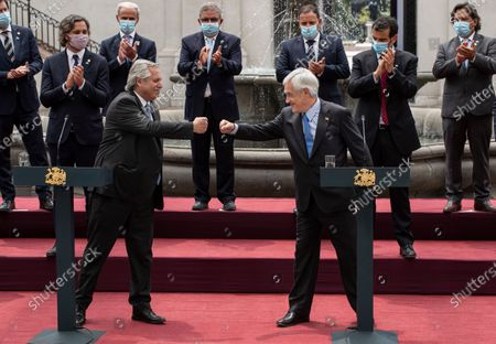 Argentina's President Alberto Fernandez, left, and Chile's President Sebastian Pinera bump fists at La Moneda presidential palace in Santiago, Chile, . Fernandez is in an official visits to Chile for two days