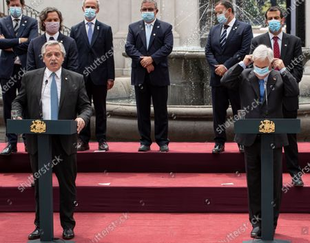 Argentina's President Alberto Fernandez, left, talks while Chile's President Sebastian Pinera puts on a mask during a joint statement at La Moneda presidential palace in Santiago, Chile, . Fernandez is on an official visit to Chile for two days