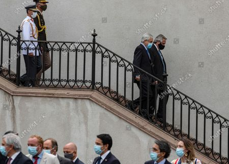 Chile's President Sebastian Pinera, second from right, and Argentina's President Alberto Fernandez, descend the stairs to make a joint statement at La Moneda presidential palace in Santiago, Chile, amid the COVID-19 pandemic. Fernandez is on an official visit to Chile for two days