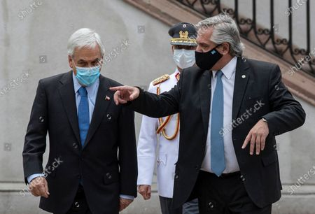 Chile's President Sebastian Pinera, left, and Argentina's President Alberto Fernandez walks prior to giving a joint statement at La Moneda presidential palace in Santiago, Chile, amid the COVID-19 pandemic. Fernandez is on an official two-day visit to Chile