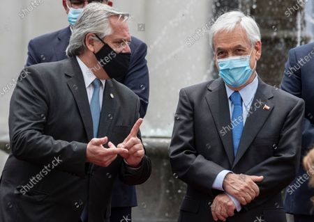 Argentina's President Alberto Fernandez, left, and Chile's President Sebastian Pinera talks prior to giving a joint statement at La Moneda presidential palace in Santiago, Chile, . Fernandez is on an official two-day visit to Chile