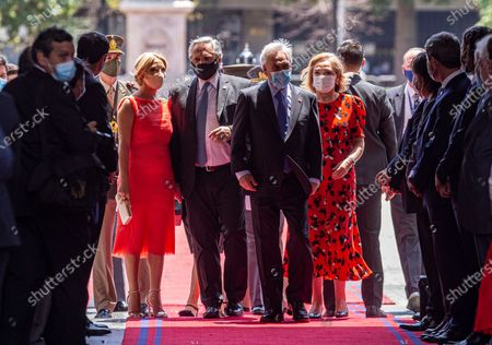 Argentina's President Alberto Fernandez, second from left, and his wife Marcela Luchetti are received by Chile's President Sebastian Pinera and his wife Cecilia Morel, at La Moneda presidential palace in Santiago, Chile, . Fernandez is on an official visit to Chile for two days