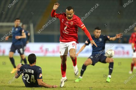 Al-Ahly player Magdy Afsha (M) in action against Pyramids player Ahmed Fathi (L) during the Egyptian Premier League soccer match between Al-Ahly and Pyramids at June 30 Stadium in Cairo, Egypt, 26 January 2021.
