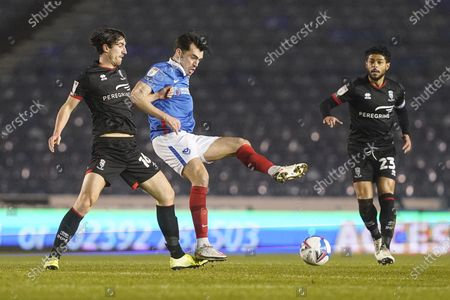 John Marquis of Portsmouth is tackled by Joe Walsh of Lincoln City during the EFL Sky Bet League 1 match between Portsmouth and Lincoln City at Fratton Park, Portsmouth