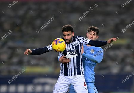 West Bromwich Albion's Hal Robson-Kanu, front, duels for the ball with Manchester City's John Stones during the English Premier League soccer match between West Bromwich Albion and Manchester City at the Hawthorns stadium in West Bromwich, England