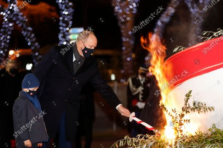 Stock Image of Monaco's Prince Albert II (R) and his son Prince Jacques set fire to a fishing boat during the traditional celebration of St. Devote in Monaco, 26 January 2021. It is since 1924 and under the reign of Prince Louis II that a fishing boat has been burnt on the evening of 26 January. Saint Devote is the patron saint of Monaco.