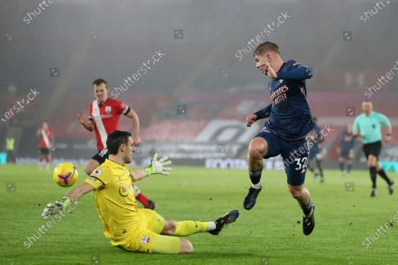 Arsenal's Emile Smith Rowe, right, tries to beat Southampton's goalkeeper Alex McCarthy during an English Premier League soccer match between Southampton and Arsenal at the St Mary's stadium in Southampton, England