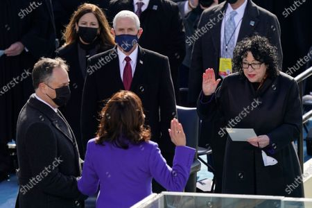 Stock Picture of Kamala Harris is sworn in as Vice President by Supreme Court Justice Sonia Sotomayor as her husband Doug Emhoff holds the Bible during the 59th Presidential Inauguration at the U.S. Capitol in Washington, . Vice President Mike Pence and his wife Karen Pence look on