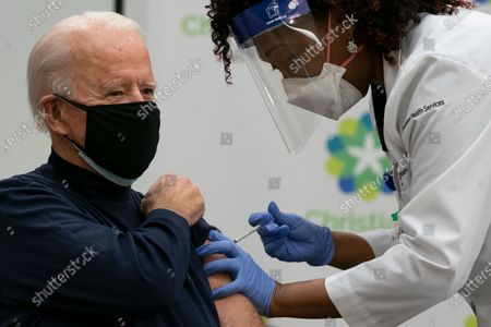 US President-elect Joe Biden receives a Covid-19 vaccination from Tabe Mase, Nurse Practitioner and Head of Employee Health Services, at the Christiana Care campus