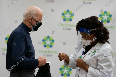 US President-elect Joe Biden celebrates with Tabe Mase, Nurse Practitioner and Head of Employee Health Services after receiving a Covid-19 vaccination at the Christiana Care campus