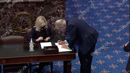 In this image from United States Senate television, US Senate Majority Leader Chuck Schumer (Democrat of New York) signs the oath book to serve as an impeachment juror during the second impeachment trial of former US President Donald Trump in the US Senate in the US Capitol in Washington, DC.