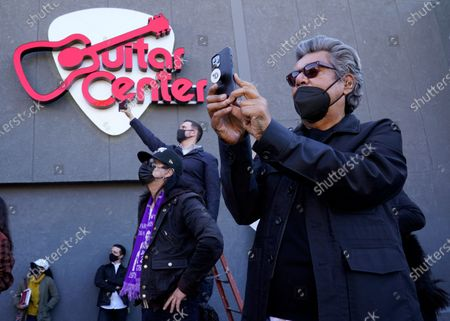 Stock Picture of Actor/comedian George Lopez photographs the unveiling of a mural by artist Robert Vargas honoring the late guitarist Eddie Van Halen at Guitar Center Hollywood on what would have been the musician's 66th birthday, in Los Angeles. Van Halen died of a stroke in October