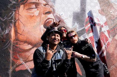 Artist Robert Vargas, left, is joined by Marq Torien, center, of the band BulletBoys and Jesse Hughes of Eagles of Death Metal at the unveiling of Vargas' mural honoring the late guitarist Eddie Van Halen at Guitar Center Hollywood on what would have been the musician's 66th birthday, in Los Angeles. Van Halen died of a stroke in October