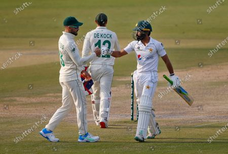 South Africa's Faf du Plessis, left, congratulates Pakistan's Fawad Alam, on scoring a century while he walks back to the pavilion after his dismissal during the second day of the first cricket test match between Pakistan and South Africa at the National Stadium, in Karachi, Pakistan