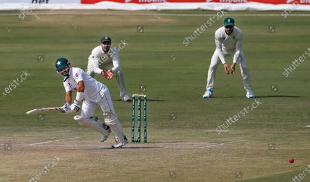 Pakistan's batsman Mohammad Rizwan, left, follows the ball after playing a shot while South Africa's Faf du Plessis, right, and Aiden Markram watches during the second day of the first cricket test match between Pakistan and South Africa at the National Stadium, in Karachi, Pakistan