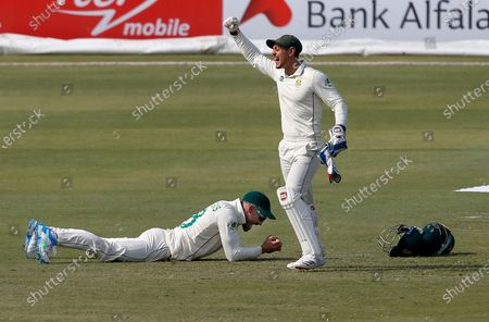 South Africa's Quinton de Kock, right, and Faf du Plessis react after the dismissal of Pakistan's batsman Mohammad Rizwan during the second day of the first cricket test match between Pakistan and South Africa at the National Stadium, in Karachi, Pakistan