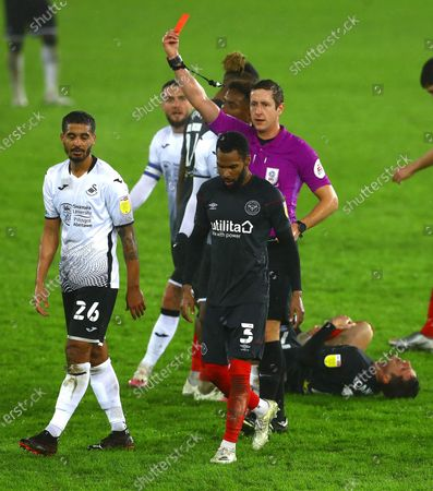 Kyle Naughton of Swansea City is shown a red card for a second bookable offence after a foul on Sergi Canos of Brentford