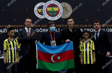 Fenerbahce's new transfer Mesut Oezil (3-R) holds and Azerbaijan flag as he poses with Fenerbahce's President Ali Koc (L) and sporting director Emre Belozoglu (R) during the signing ceremony in Istanbul, Turkey, 27 January 2021. Oezil signed a contract until summer 2024.