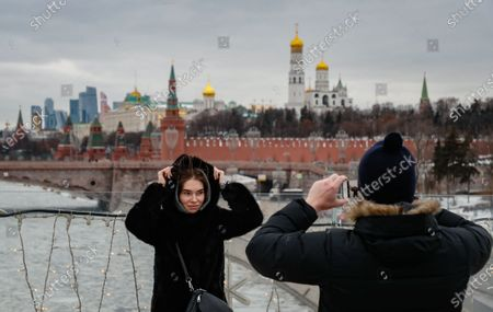 Tourists are photographed against the background of the Kremlin in Moscow, Russia, 27 January 2021. Moscow Mayor Sergei Sobyanin canceled the requirement to transfer at least 30% of the staff to remote operation. Also, in accordance with the decree, the ban on night work of clubs and catering establishments from January 27 was canceled.