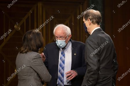 Sen. Bernie Sanders, D-Vt, center, speaks with Sen. Maria Cantwell, D-Wash., and Sen. Ron Wyden, D-Or., ahead of a hearing to examine the nomination of Former Michigan Governor Jennifer Granholm to be Secretary of Energy, on Capitol Hill in Washington, Wed