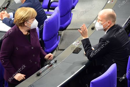 German Chancellor Angela Merkel (L) and Christian Democratic Union (CDU) and Christian Social Union (CSU) faction chairman in the German parliament Bundestag Ralph Brinkhaus (R) talk during a session of the German parliament Bundestag on the occasion of a topical debate slot about measures to cope with the COVID-19 pandemic in Berlin, Germany, 27 January 2021.