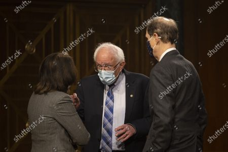 Stock Image of US Senator Bernie Sanders (C), D-Vermont, speaks with US Senator Maria Canrtwell (L), D-WA, and US Senator Ron Wyden (R), D-OR, ahead of a hearing to examine the nomination of Former Michigan Governor Jennifer Granholm to be Secretary of Energy, on Capitol Hill in Washington, DC,.