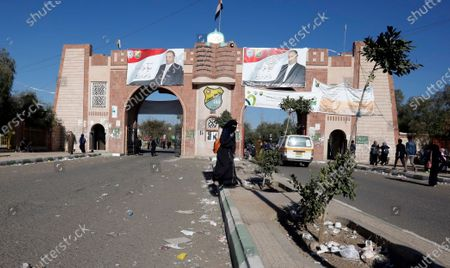 Yemenis pass the main gate of Sana'a University, with banners depicting the portraits of slain top Houthi leader saleh ali al-sammad, where a two-year-long 2011-uprising protest camp was set up, ahead of the tenth anniversary of the uprising, in Sana'a, Yemen, 20 January 2021 (issued 27 January 2021). Yemen on 27 January 2021 marks the 10th anniversary of the 2011 Arab Spring uprising that toppled the then-president Ali Abdullah Saleh.