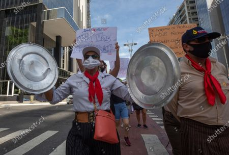 Woman shouts slogans as she bangs pan lids during a protest organized by restaurants and bar workers against restrictions on restaurants imposed by the Sao Paulo state government to help contain the spread of the new coronavirus in Sao Paulo, Brazil, . According to new rules imposed by Governor Joao Doria, restaurants and bars can operate until 8 p.m. on weekdays and must close on weekends