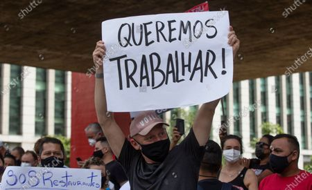 """Restaurant worker holds a banner that reads in Portuguese """"We want to work,"""" during a protest organized by restaurant and bar workers against restrictions on restaurants imposed by the Sao Paulo state government to help contain the spread of the new coronavirus in Sao Paulo, Brazil, . According to new rules imposed by Governor Joao Doria, restaurants and bars can operate normally until 8 p.m. on weekdays and must close on weekends"""