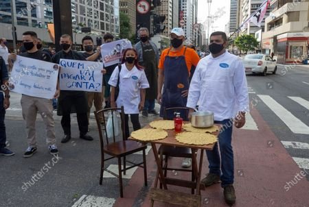 Restaurants and bar workers with signs and a mock restaurant table protest restrictions on restaurants imposed by the Sao Paulo state government to help contain the spread of the new coronavirus in Sao Paulo, Brazil, . According to new rules imposed by Governor Joao Doria, restaurants and bars can operate normally until 8 p.m. on weekdays and must close on weekends