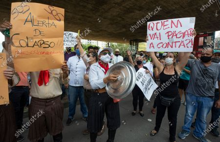 """Restaurants and bar workers hold up Portuguese protest messages """"SOS. Collapse alert"""" and """"Who's going to pay the tab?,"""" as they protest restrictions imposed by the Sao Paulo state government to help contain the spread of the new coronavirus in Sao Paulo, Brazil, . According to new rules imposed by Governor Joao Doria, restaurants and bars can operate normally until 8 p.m. on weekdays and must close on weekends"""